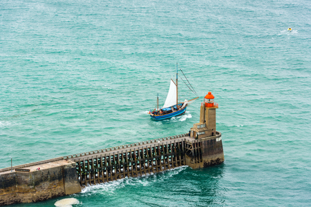 normandy: View of an Old Pier with lighthouse and a sailboat in Fecamp, France