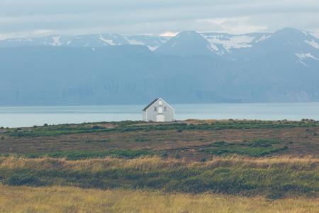 Siding cottage at coastline in East Iceland.
