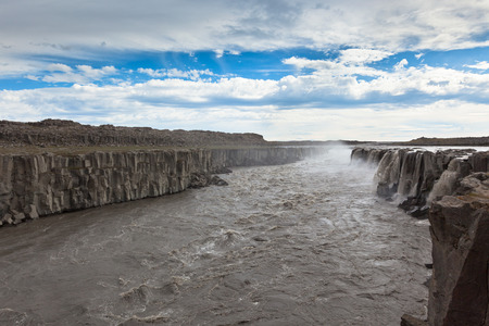 Dettifoss Waterfall in Iceland under a blue summer sky with clouds