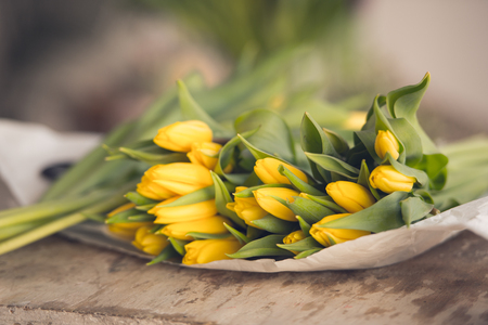 Yellow tulips flowers bouquet on a wooden table. Indoors natural light shot with small depth of field