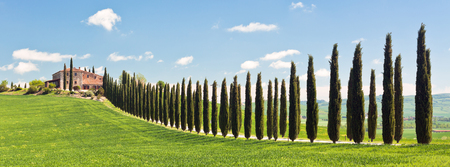Classic view of Tuscan farmhouse, green field and cypress tree rows. Long wide banner