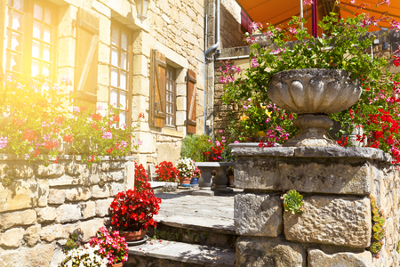 Bright flower pots on an ancient stone house porch in Southern France Stock Photo