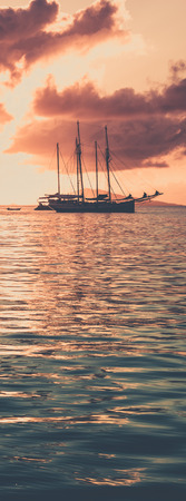 Recreational Yacht at the Indian Ocean. Beautiful sunset. Polaroid like toned shot. Vertical banner