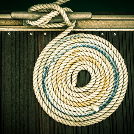 A mooring rope with a knotted end tied around a cleat on a wooden pier