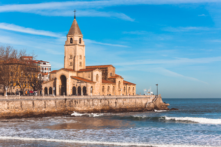 View of San Lorenzo ocean beach and San Pedro church in Gijon, Asturias, the Northern Spain