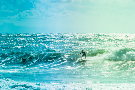 Extreme surfers riding some waves on the sea in France Stock Photo