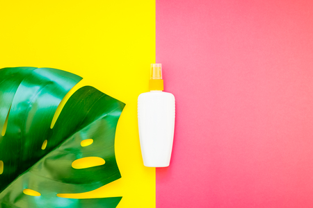 Tropical jungle palm monstera leaves and sunscreen blank bottle mockup on bright yellow and pink duotone paper background. Summer vacations creative flat lay concept template for text