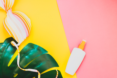 Tropical jungle palm monstera leaves, sunglasses, sunscreen blank bottle mockup and womans swimsuit top on bright color paper background. Summer vacations creative flat lay concept template for text