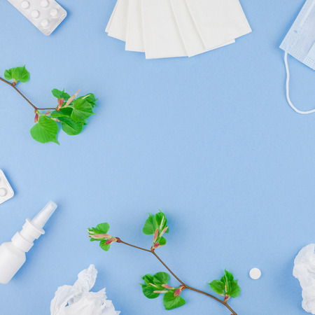 Creative flat lay concept of seasonal spring pollen allergy with napkins, pills, face mask, drops in a bottle and fresh green sprouts with buds. Stock Photo
