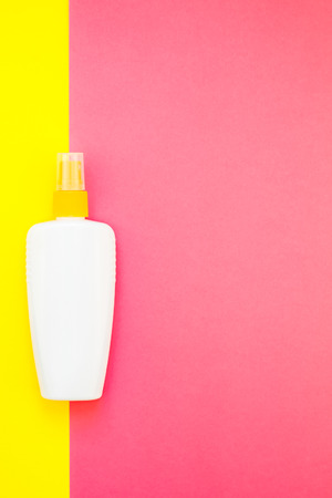 Sunscreen blank bottle mockup on bright yellow and pink duotone paper background. Summer vacations creative flat lay concept template for text