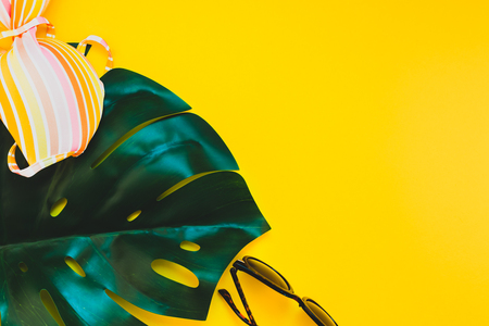 Tropical jungle palm monstera leaves, sunglasses and a womans swimsuit top on bright yellow paper background. Summer vacations creative flat lay concept template for text