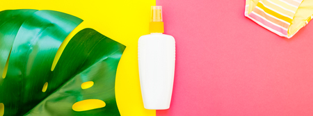 Tropical jungle palm monstera leaves, sunscreen blank bottle mockup and womans swimsuit on bright color paper background. Summer vacations creative flat lay concept template text. Long wide banner Stock Photo