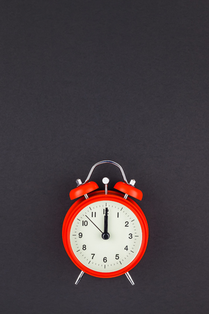 Concept image of a red vintage alarm clock with twelve o clock on dark black color paper background