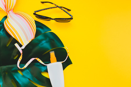 Tropical jungle palm monstera leaves, sunglasses, sunscreen blank bottle mockup and womans swimsuit top on bright yellow paper background.