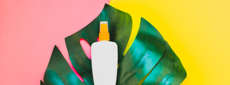 Tropical jungle palm monstera leaves and sunscreen blank bottle mockup on bright yellow and pink duotone paper background. Summer vacations creative flat lay concept template text. Long wide banner