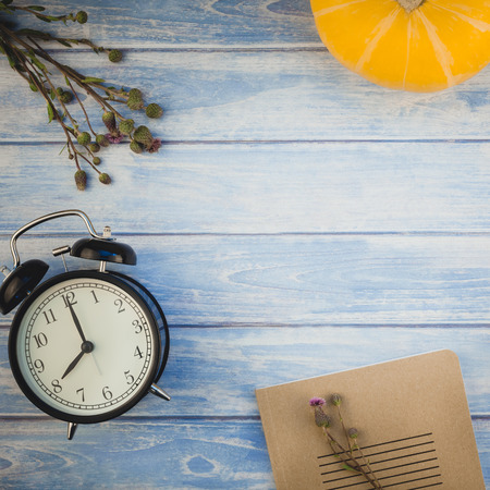 Square Top view of autumn orange pumpkins and dry flowers and grass thanksgiving background over blue toned wooden table with copy space. Template for fall harvest mood text
