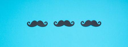 Creative flatlay overhead top view retro stylish black paper photo booth props moustaches turquoise background copy space. Men health awareness month fathers day masculinity concept long wide banner Stock Photo