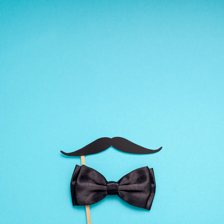 Creative square flatlay overhead top view retro black paper photo booth props moustaches turquoise background copy space.