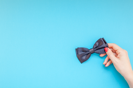 Creative flatlay top view retro black bow tie woman hands turquoise paper background copy space. Stock Photo