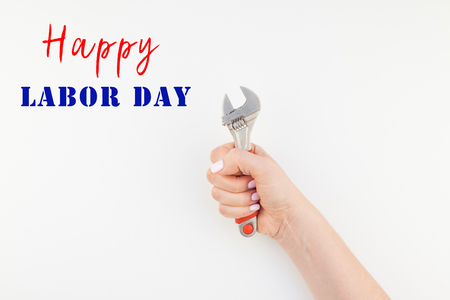 Creative image of woman hand with pastel manicure polish holding spanner with copy space isolated on white background in minimalism style.