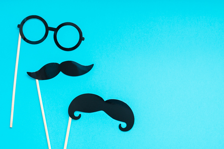 Creative flatlay overhead top view retro stylish black paper photo booth props moustaches turquoise background copy space. Stock Photo