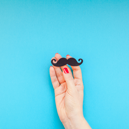 Creative square flatlay top view retro black paper photo booth props moustaches woman hands turquoise background copy space