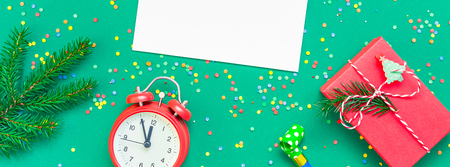 New Year or Christmas mock up flat lay top view with red alarm clock twelve midnight fir tree branch Xmas holiday celebration green paper bright colorful confetti Long wide banner. Stock Photo