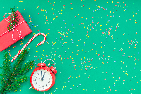 New Year or Christmas pattern flat lay top view with red alarm clock twelve midnight fir tree branch Xmas holiday celebration green paper bright colorful confetti background.