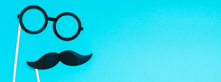 Creative long wide banner top view retro stylish black paper photo booth props moustaches turquoise background copy space.