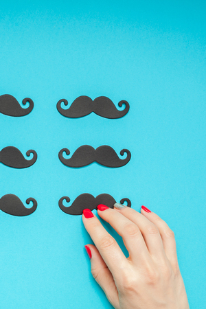 Creative flatlay overhead top view retro stylish black paper photo booth props moustaches turquoise female hand background copy space. Men health awareness month fathers day masculinity concept