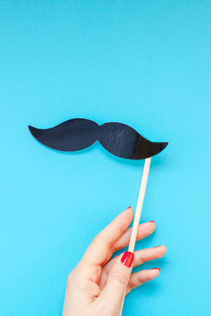 Creative flatlay top view retro black paper photo booth props moustaches woman hands turquoise background copy space. Men health awareness month fathers day masculinity concept blog social media
