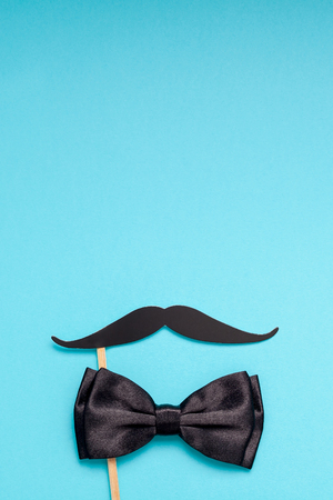 Creative flatlay overhead top view retro stylish black paper photo booth props moustaches turquoise background copy space. Men health awareness month fathers day masculinity concept blog social media
