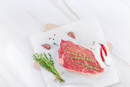 Creative Top view flat lay of fresh raw beef meat striploin steak rosemary thyme herbs garlic meat pepper mushrooms white marble table background with copy space. Food meat preparation cooking concept Stock Photo