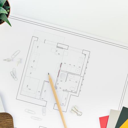 Kreative Wohnung lag oben Draufsicht Blaupausen architektonische Wohnung Projektplan und Büromaterial auf Dekorator Quadrat weißen Tisch Arbeitsbereich Farbfelder Werkzeuge und Ausrüstung Hintergrund Kopie Raum Konzept