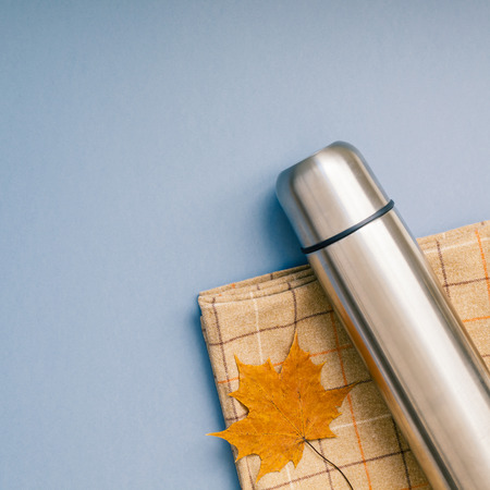 Creative Top view flat lay outdoors trip composition. Thermos blanket autumn leaf grey blue background copy space. Square Template weekend outing picnic nature tourism recreation