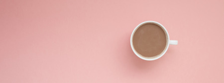 Creative autumn flat lay overhead top view coffee milk latte cup on millennial pink background copy space minimal style. Fall season template for feminine blog social media Long wide banner
