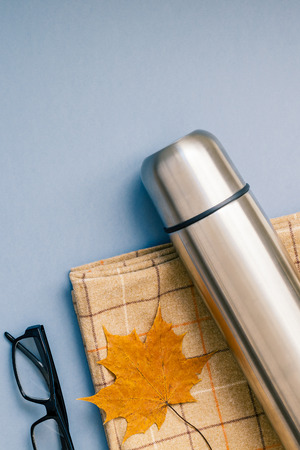Creative Top view flat lay outdoors trip composition. Thermos blanket autumn leaf grey blue background copy space. Template weekend outing picnic nature tourism recreation