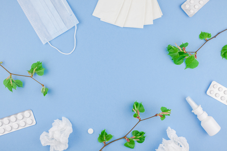 Creative flat lay concept of seasonal spring pollen allergy with napkins, pills, face mask, drops in a bottle and fresh green sprouts with buds. copy space background minimal style, template for text