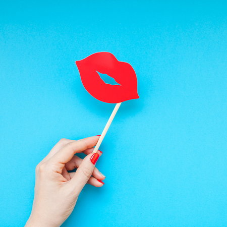 Creative overhead top view retro stylish red paper photo booth props female lips in hand turquoise background copy space. Birthday parties and weddings valentine day square template