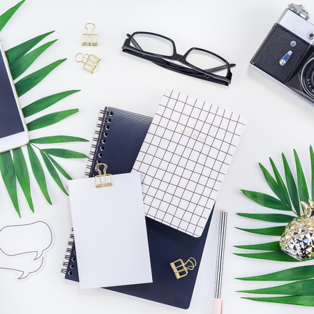 Top view flat lay office workspace desk styled design office supplies alarm clock tropical palm leaves smartphone camera copy space black white background. Square office feminine blog social media