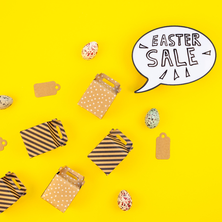 Creative Top view flat lay holiday promo composition Easter sale bunny ears gift boxes eggs text message on bold yellow paper background copy space Template Easter day seasonal minimal concept