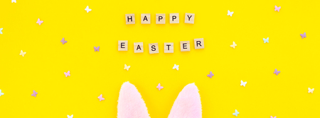 Creative Top view flat lay holiday composition Easter bunny ears eggs text message on bold yellow paper background copy space Template Easter day seasonal minimal concept pattern Stock Photo