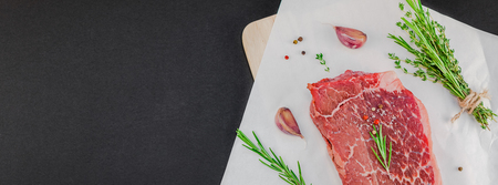 Creative Top view flat lay of fresh raw beef meat striploin steak with rosemary thyme herbs garlic pepper mushrooms black background with copy space. Food preparation cooking concept Long wide banner Stock Photo