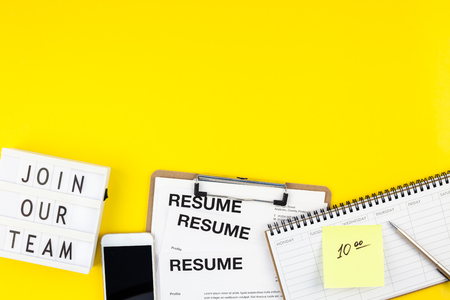 Creative top view flat lay of desk with join our team text on lightbox copy space on bold yellow background in minimal style. Concept of new job, hiring recruitment process, new team members screening 版權商用圖片