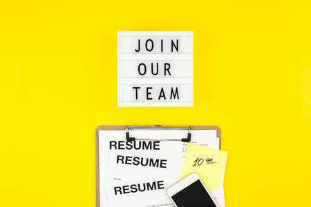 Creative top view flat lay of desk with join our team text on lightbox copy space on bold yellow background in minimal style. Concept of new job, hiring recruitment process, new team members screening 스톡 콘텐츠