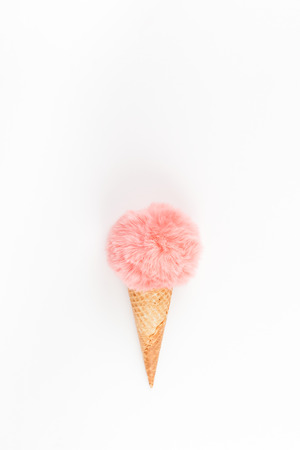 Creative top view flat lay of coral color fluffy fur ball in ice cream waffle cone with copy space on white background in minimal style. Concept feminine blog social media. Natural light with shadows Imagens