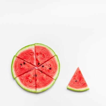 Kreative skandinavische flache Draufsicht auf frische Wassermelonenscheiben auf weißem Tischhintergrund-Kopierraum. Minimale Sommerfrüchte kreativ für Blog oder Rezeptbuch