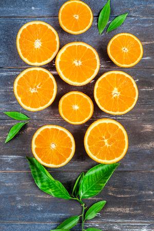 Creativo stile scuro laici piatta vista dall'alto di fette di frutta arancione fresca su sfondo tavolo in legno marrone con spazio copia. Composizione minimale estiva di agrumi freschi per blog o ricettario Archivio Fotografico