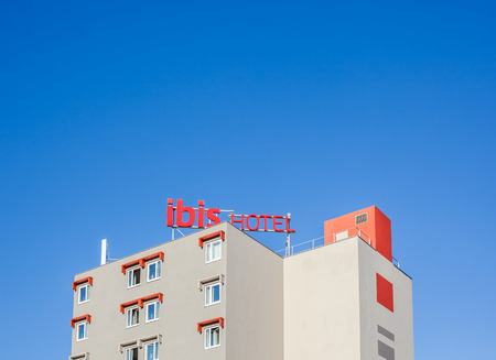 BEZIERS, FRANCE - FEBRUARY 26, 2018: Ibis logo at hotel building located in Beziers, France. Bright blue sky with copy space background
