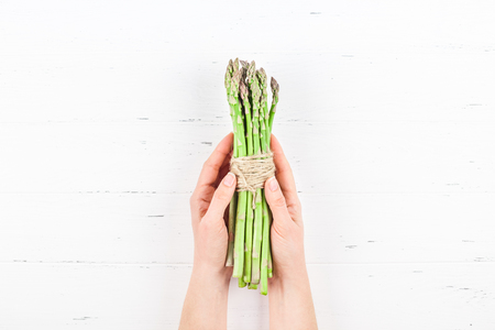 Creative scandinavian style flat lay top view of fresh green asparagus in woman hands on white wooden table background copy space. Minimal house cooking concept for blog or recipe book